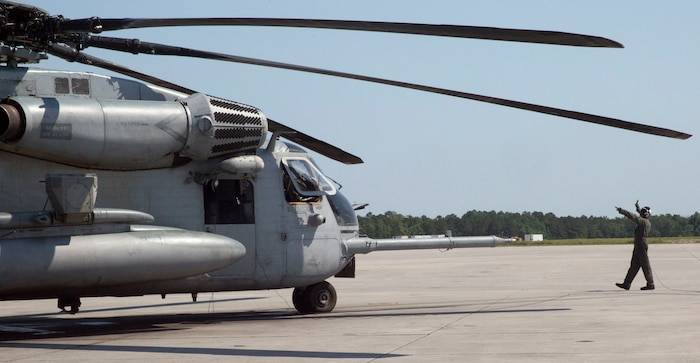 A Marine gives signals to the pilots of a CH-53 Super Stallion before taking off for a ceremony at Marine Corps Air Station New River, N.C., May 17, 2017.  The ceremony marks the reopening of Landing Zone Vulture, which closed Sept. 2, 2015 after a CH-53 crashed resulting in the death of one Marine.  The instructors took the opportunity to memorialize their fallen Marine, Staff Sgt. Jonathan Lewis, through the sustainment rappel. The Marines are with EOTG, II Marine Expeditionary Force Headquarters Group.