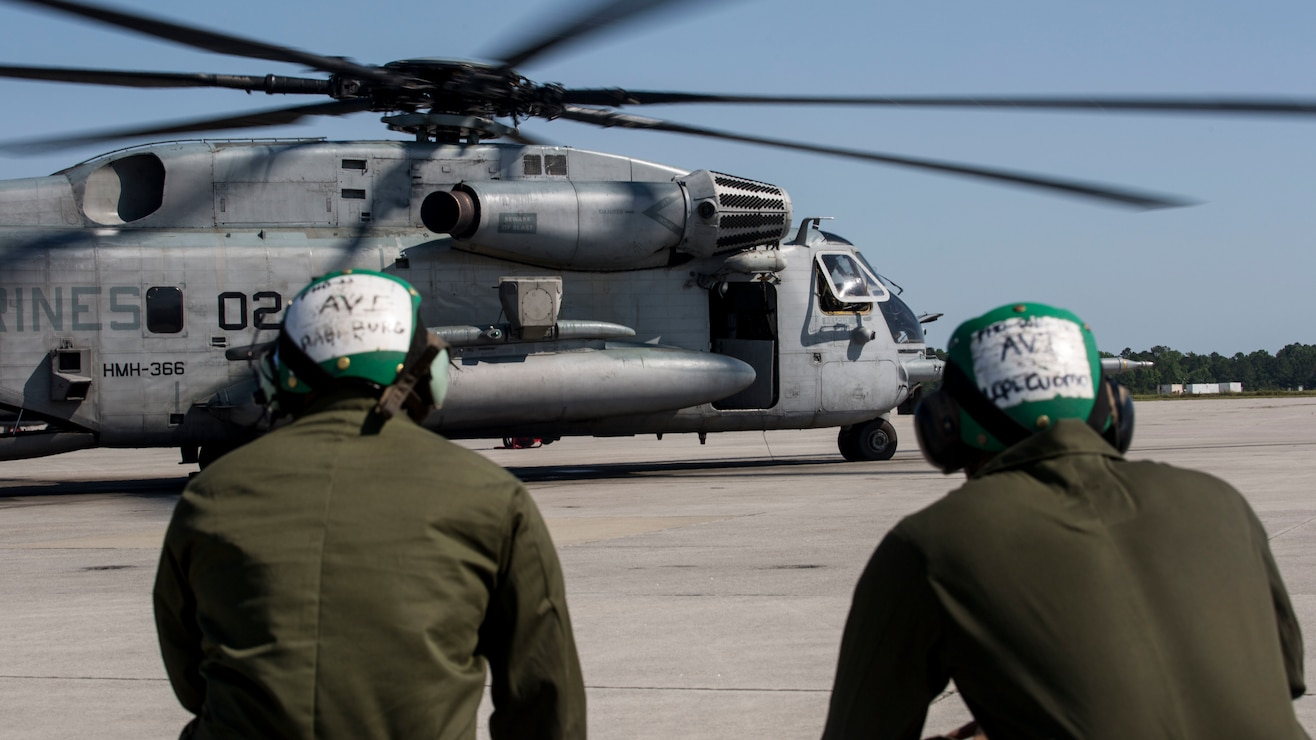 Two Marines observe the CH-53 Super Stallion as it prepares to take off for a ceremony at Marine Corps Air Station New River, N.C., May 17, 2017.  The ceremony marks the reopening of Landing Zone Vulture, which closed Sept. 2, 2015 after a CH-53 crashed resulting in the death of one Marine.  The instructors took the opportunity to memorialize their fallen Marine, Staff Sgt. Jonathan Lewis, through the sustainment rappel. The Marines are with EOTG, II Marine Expeditionary Force Headquarters Group.