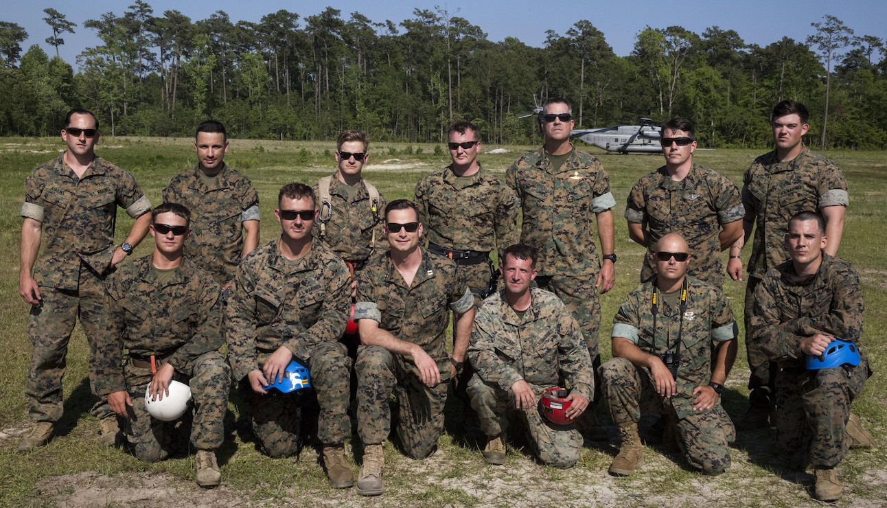 Marines gather in front of a CH-53 Super Stallion at Landing Zone Vulture after rappelling during a ceremony at Stone Bay, a Camp Lejeune satellite training area, N.C., May 17, 2017.  The ceremony marks the reopening of Landing Zone Vulture, which closed Sept. 2, 2015 after a CH-53 crashed resulting in the death of one Marine.  The instructors took the opportunity to memorialize their fallen Marine, Staff Sgt. Jonathan Lewis, through the sustainment rappel. The Marines are with EOTG, II Marine Expeditionary Force Headquarters Group.