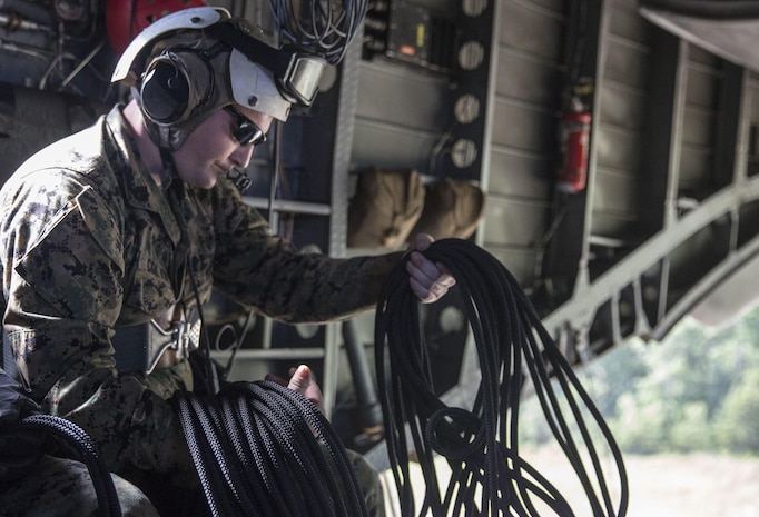 Staff Sgt. Jerry Colvin unravels a rope before rappelling out of a CH-53 Super Stallion during a ceremony at Stone Bay, a Camp Lejeune satellite training area, N.C., May 17, 2017.  The ceremony marks the reopening of Landing Zone Vulture, which closed Sept. 2, 2015 after a CH-53 crashed resulting in the death of one Marine.  The instructors took the opportunity to memorialize their fallen Marine, Staff Sgt. Jonathan Lewis, through the sustainment rappel. Staff Sgt. Colvin is with EOTG, II Marine Expeditionary Force Headquarters Group.
