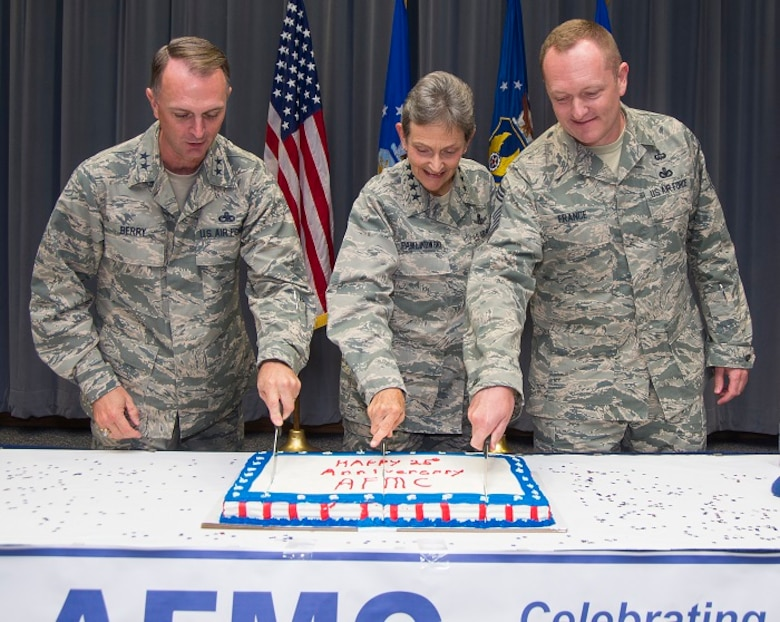 Gen. Ellen M. Pawlikowski (center), commander of Air Force Materiel Command; Maj. Gen. Warren D. Berry, AFMC vice commander, and Chief Master Sgt. Jason France, AFMC command chief, prepare to cut a cake commemorating AFMC's 25th anniversary. A brief ceremony marking the occasion took place in Headquarters AFMC's Sarris Auditorium July 10, 2017. The command's 25th birthday was July 1. On July 1, 1992, Air Force Logistics Command and Air Force Systems Command combined to form AFMC, a single, streamlined organization with an expanded mission. The new command built upon AFLC's expertise in providing worldwide logistics support -- including maintenance, modification and overhaul of weapon systems -- and AFSC's expertise in science, technology, research, development and testing. (U.S. Air Force photo/R.J. Oriez)