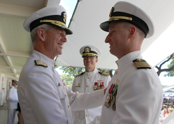 Vice Adm. Thomas Moore, Commander Naval Sea Systems Command, congratulates Capt. Jamie Kalowsky on Kalowsky's relief as commanding officer of Pearl Harbor Naval Shipyard and Intermediate Maintenance Facility.  The 47th and new commanding officer, Capt. Greg Burton looks on.  The change of command took place in front of the Shipyard Headquarters Building on Friday, July 7, 2017.