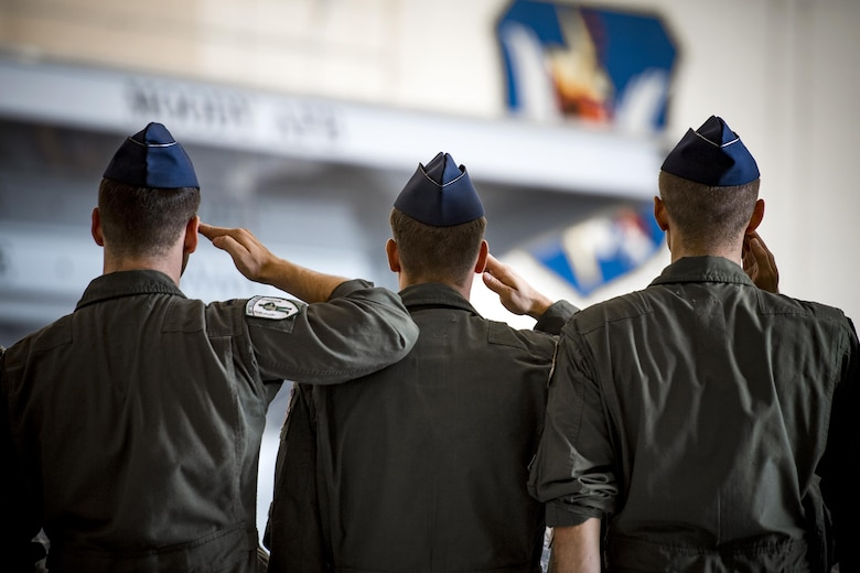 Airmen from the 41st Rescue Squadron salute during a change of command ceremony, July 10, 2017, at Moody Air Force Base, Ga. The change of command ceremony is a part of military history signifying the hand-off of responsibility of a unit from one commander to another. (U.S. Air Force photo by Staff Sgt. Ryan Callaghan)