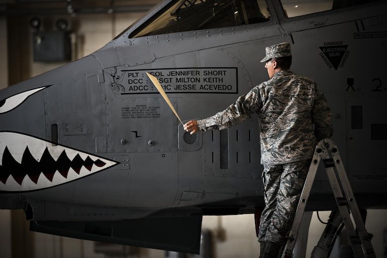 Airman 1st Class Jesse Acevedo, 75th Aircraft Maintenance Unit crew chief, reveals a name plate for Col. Jennifer Short, 23d Wing commander, during a change of command ceremony, July 10, 2017, at Moody Air Force Base, Ga. This ceremony marked the first time a female will command the unit and the first time a fighter pilot will command the 23d Wing since its reactivation at Moody in 2006. (U.S. Air Force photo by Staff Sgt. Ryan Callaghan)