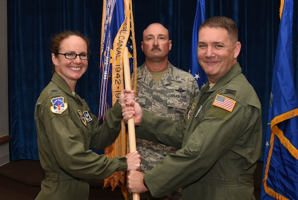 Colonel Stacy Huser, 90th Missile Wing commander, passes the guidon to Col. Robert Ewers, 90th Operations Group commander, during the 90th OG change of command ceremony at F.E. Warren Air Force Base, Wyo., July 10, 2017. The ceremony signified the transition of command from Col. Todd Sauls to Ewers. (U.S. Air Force photo by Airman 1st Class Breanna Carter)