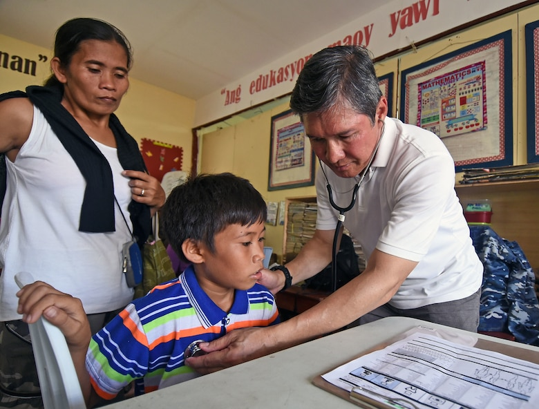 Dr. John Cinco, founder of Pacific Angel (PACANGEL), checks the vitals of a child from San Remigio during PACANGEL 2017 in Northern Cebu Province, Philippines, June 29, 2017. PACANGEL is a multilateral humanitarian assistance civil military engagement, which improves military-to-military partnerships in the Pacific while also providing medical health outreach, civic engineering projects and subject matter exchanges among partner forces. (U.S. Air Force photo/Master Sgt. Jeff Andrejcik)