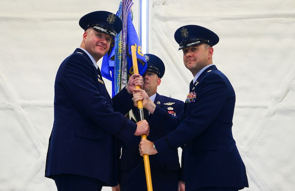 Col. Richard Carrel, 59th Operations Group commander, passes the 36th Rescue Squadron guidon to Lt. Col. Chad Kohout, 36th RQS commander, during a change of command ceremony July 7, 2017, at Fairchild Air Force Base, Washington. Kohout assumed command from Lt. Col. Jason Snyder. (U.S. Air Force photo/Senior Airman Janelle Patiño)