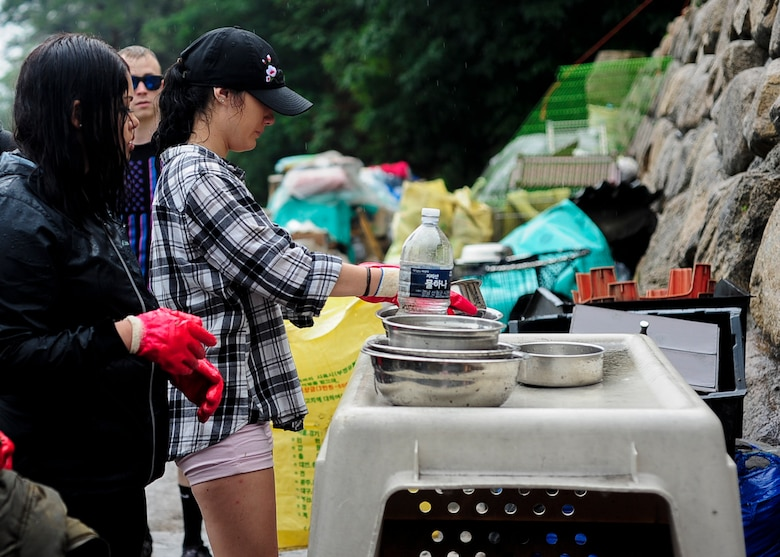U.S. Air Force Airmen assigned to Kunsan Air Base, Republic of Korea and other volunteers wash out water bowls while on a volunteer trip to an animal shelter in Daegu, RoK, July 8, 2017. The trip, sponsored by Kunsan Patriots for Animal Welfare and Scholarships, or Kunsan P.A.W.S., was the first of many to the no-kill shelter in Daegu. (U.S. Air Force photo by Staff Sgt. Victoria H. Taylor)