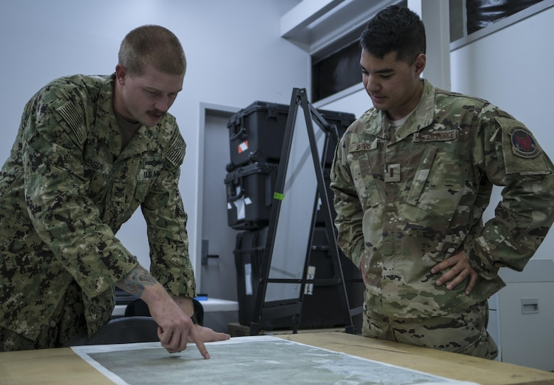 A U.S. Navy Helicopter Sea Combat Squadron-85 intelligence analyst points out locations on a map of Central Queensland in Australia to a U.S. Air Force 1st Special Operations Squadron intelligence officer, as the analysts build the intelligence picture for the warfighting scenario of Talisman Saber 2017, July 10, 2017 at Rockhampton, Australia. Aside from service components working with the Australian military, the exercise also provided an opportunity for U.S. forces to integrate intelligence systems and share tactics, trainings and procedures with other U.S. services. (U.S. Air Force photo by Capt. Jessica Tait)