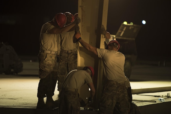 Airmen assigned to the 557th Expeditionary RED HORSE hold a vertical column in place as it is being secured June 27, 2017, in Southwest Asia. The squadron is tasked with constructing a new 332nd Air Expeditionary Wing mission support industrial complex and life support area, to include facilities, utilities and roads, providing the wing with increased capabilities. (U.S. Air Force photo/ Senior Airman Damon Kasberg)