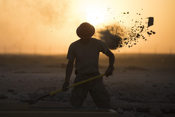 Staff Sgt Dominic Koah, 557th Expeditionary RED HORSE water fuels system maintenance craftsman, shovels dirt and concrete away from a construction site June 27, 2017, in Southwest Asia. Working through extreme heat and high winds members of RED HORSE construct pre-engineered buildings vital to the expansion of the 332nd Air Expeditionary Wing and its operational capabilities. (U.S. Air Force photo/Senior Airman Damon Kasberg)