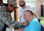 Air Force Master Sgt. Nikki Broomfield, military human resources specialist, Resource Management Division, Command Support Directorate, DLA Aviation, attaches a pin to Henry Pleasants, a World War II veteran who suffers from Alzheimer's, after an Independence Day ceremony to honor veterans at the Dunlop Home assisted living facility, in Colonial Heights, Virginia July 6, 2017.