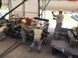Staff Sgt. Corey Ledford, from the 137th Air Refueling Wing, pulls the hoist chain while lifting two Mk-82 bombs on a trailer during the competition week of the Air National Guard Ammo Rodeo that took place at Volk Field Air National Guard base June 18-July 1.
