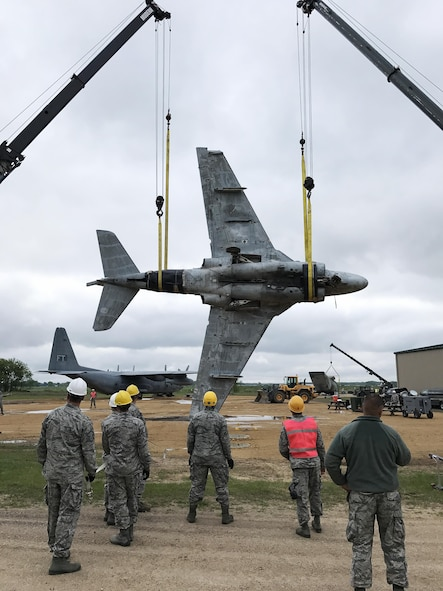 Students lift a 21,000 pound decommissioned A-6E Intruder Navy plane during a Crash Damage or Disabled Aircraft Recovery (CDDAR) training course at Volk Field Air National Guard base on May 23. In the simulation, the aircraft was found upside down and students must rig the aircraft and conduct a complex lift and roll maneuver. During the procedure, the appointed team chief, who is also a student in the class, coordinates the task with the two crane operators. Wisconsin National Guard photo by Maj. Penny Ripperger