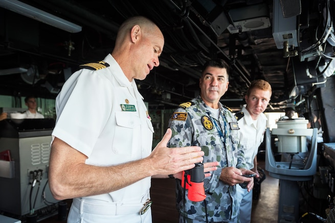 Navy Capt. Nate Moyer, commanding officer of the amphibious transport dock ship USS Green Bay, left, and Cmdr. Peter Mellick, assigned to the Royal Australian Navy, discuss ship maneuvers during a sea and anchor detail in Cairns, Australia, June 28, 2017. The Green Bay, part of the Bonhomme Richard Expeditionary Strike Group, is operating in the Indo-Asia-Pacific region to enhance bilateral partnerships. Navy photo by Petty Officer 3rd Class Sarah Myers