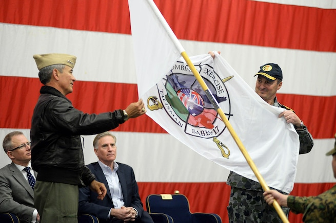 Navy Adm. Harry B. Harris, commander of U.S. Pacific Command, left, and Royal Australian Navy Vice Adm. David Johnston, chief of joint operations, unfurl the ceremonial Talisman Saber 2017 flag during the Talisman Saber 2017 opening ceremony aboard the amphibious assault ship USS Bonhomme Richard, June 29, 2017. Navy photo by Petty Officer 2nd Class Sarah Villegas