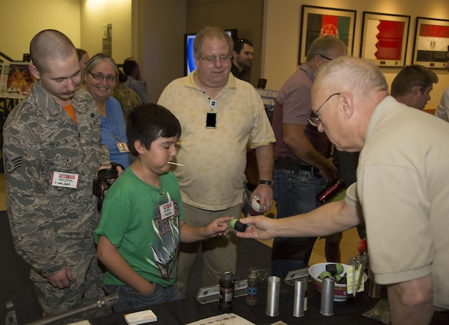 Mr. Paul Burke, Joint Non-Lethal Weapons Directorate Combatant Command Liaison Officer to U.S. Special Operations Command, demonstrates the payload of a 40mm sponge grenade round to one of the participants at the U.S. Central Command Family Day on June 16.