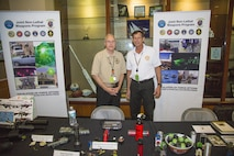 Mr. Paul Burke, Joint Non-Lethal Weapons Directorate Combatant Command (COCOM) Liaison Officer to U.S. Special Operations Command (left), and Mr. Rick Bartis, COCOM Liaison Officer to U.S. Central Command (CENTCOM), stand behind the non-lethal weapons and munitions display at the U.S. CENTCOM Family Day. Nearly 2,500 family members attended the June 16 event.