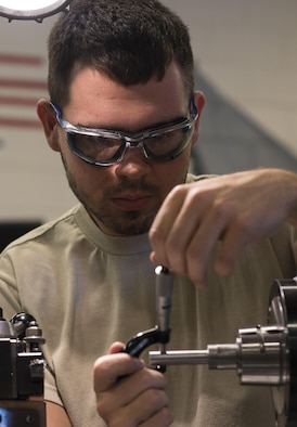 Airman 1st Class Christopher Brown, 27th Maintenance Squadron Aircraft Metals Technology apprentice, measures the width of a piece of metal in a precision lathe at Cannon Air Force Base, New Mexico, June 21, 2017. Brown has been training for the last eight months and will be finished in November. Each Airman has to be trained on every piece of equipment in the shop. (U.S. Air Force photo by Staff Sgt. Michael Washburn/Released)