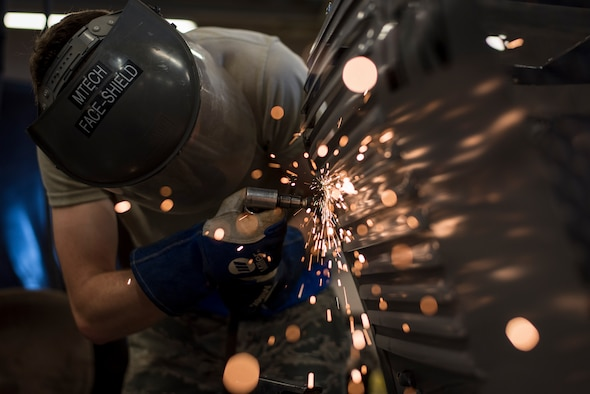 Airman 1st Class Patrick Ragan, 27th Maintenance Squadron Aircraft Metals Technology apprentice, grinds down a low-pac cover at Cannon Air Force Base, New Mexico, June 21, 2017. The cover had hair-line cracks that first needed to be filled before they were smoothed out with the grinder. (U.S. Air Force photo by Staff Sgt. Michael Washburn/Released)