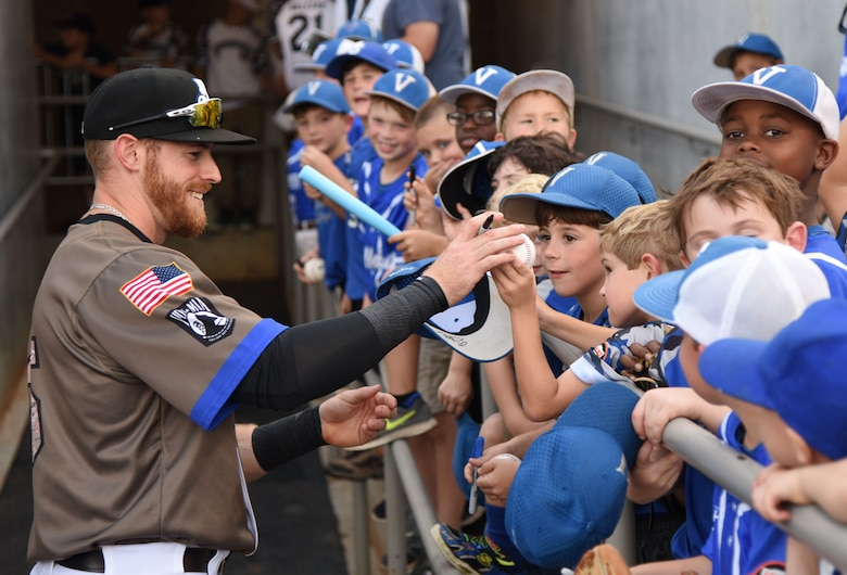 Michael Reed, Biloxi Shuckers outfielder, signs autographs for Vancleave T-ball team members during the Biloxi Shuckers Minor League Baseball team's military appreciation night July 8, 2017, in Biloxi, Miss. The Shuckers recognized and honored service members and their families for the dedication, commitment and sacrifices they make for the nation. Keesler Air Force Base leadership, Airmen and families attended the game. (U.S. Air Force photo by Kemberly Groue)