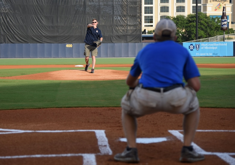 Col. C. Mike Smith, 81st Training Wing vice commander, throws the first pitch to his son, Mac, during the Biloxi Shuckers Minor League Baseball team's military appreciation night July 8, 2017, in Biloxi, Miss. The Shuckers recognized and honored service members and their families for the dedication, commitment and sacrifices they make for the nation. (U.S. Air Force photo by Kemberly Groue)