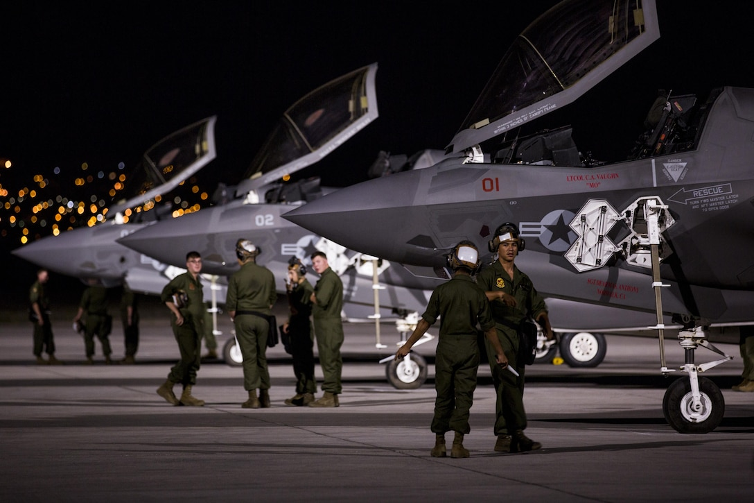 """Marines with Marine Fighter Attack Squadron (VMFA) 211 """"Wake Island Avengers,"""" 3rd Marine Aircraft Wing, wait for pilots to walk to three F-35B Lightning IIs on the first day of Red Flag 17-3 at Nellis Air Force Base, Nev., July 10. Red Flag 17-3 is a realistic combat training exercise involving the U.S. Air Force, Army, Navy and Marine Corps and this iteration is the first to have both the Air Force's F-35A Lightning II and the Marine Corps' F-35B Lightning II, which is capable of short takeoff vertical landing (STOVL). (U.S. Marine Corps photo by Sgt. Lillian Stephens/Released)"""