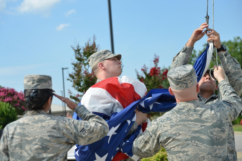 U.S. Airmen assigned to the 20th Fighter Wing (FW) detach a flag from its halyard during a retreat ceremony at Shaw Air Force Base, S.C., June 29, 2017. For the first time in 10 years, Shaw squadrons are rotating responsibility for a monthly retreat ceremony at the 20th FW headquarters. (U.S. Air Force photo by Airman 1st Class Destinee Sweeney)
