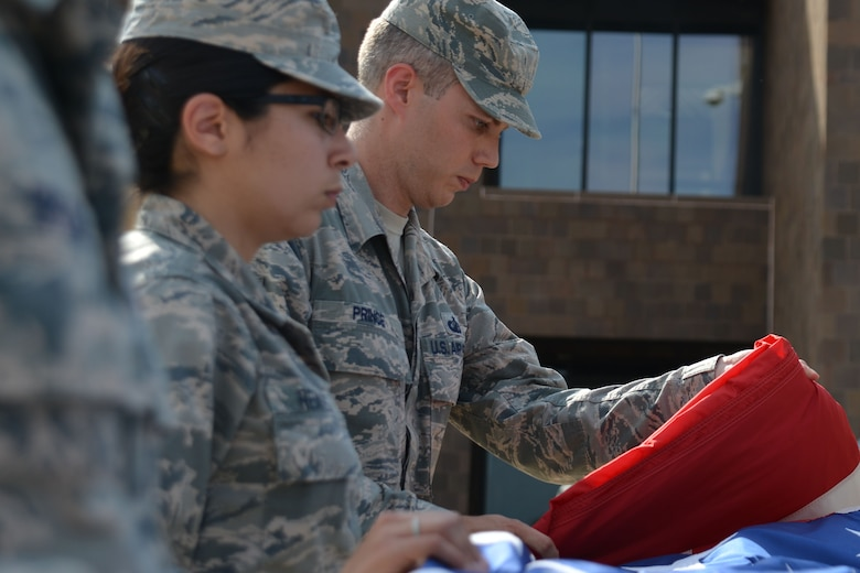 U.S. Air Force Staff Sgt. Justin Prince, 20th Comptroller Squadron finance customer service noncommissioned officer in charge, right, folds the flag during a retreat ceremony as Airman 1st Class Kathryn Reaves, 20th Fighter Wing (FW) Public Affairs photojournalist apprentice, holds the flag at Shaw Air Force Base, S.C., June 29, 2017. The flag detail will rotate amongst 20th FW squadrons on a monthly basis, giving Airmen in squadrons an opportunity to pay their respects to the flag. (U.S. Air Force photo by Airman 1st Class Destinee Sweeney)