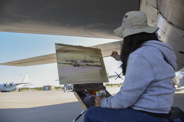 Hiu Lai Chong, artist, paints a C-130 at the Louis F. Garland Department of Defense Fire Academy on Goodfellow Air Force Base, Texas, Oct. 26, 2016. Chong was painting the C-130 as part of the EnPleinAirTEXAS competition in San Angelo, Texas. (U.S. Air Force photo by Staff Sgt. Joshua Edwards/Released)