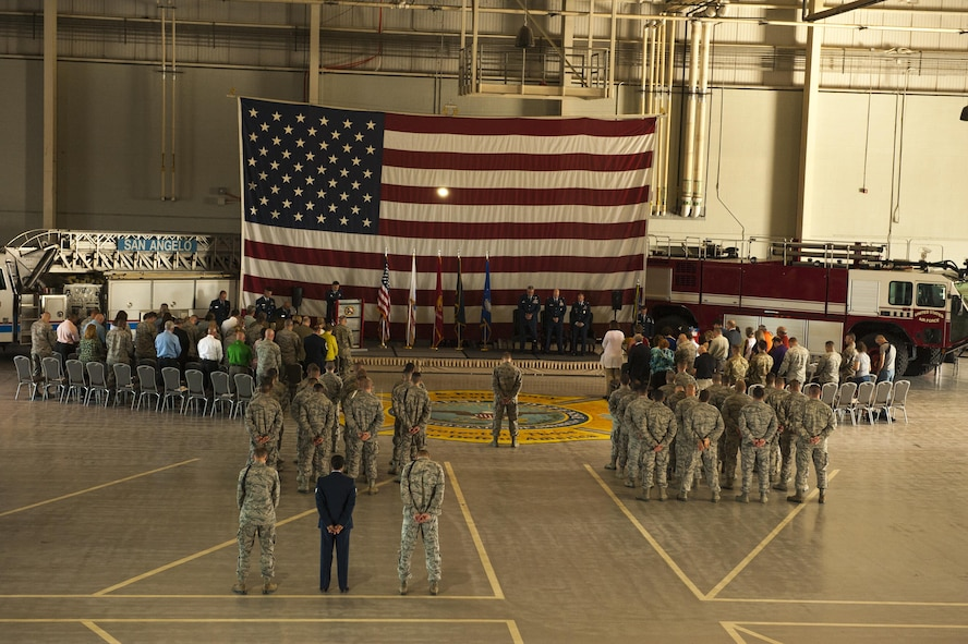 The 312th Training Squadron and visitors stand for the singing of the National Anthem during the 312th TRS change of command ceremony at the Louis F. Garland Department of Defense Fire Academy High Bay Fire Academy high bay on Goodfellow Air Force Base, Texas, July 10, 2017. The ceremony bid farewell to the previous commander, Lt. Col. Matthew Welling and welcomed the new commander, Lt. Col. Scott D. Cline. (U.S. Air Force photo by Senior Airman Scott Jackson/Released)