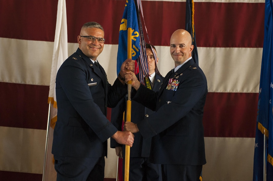 U.S. Air Force Lt. Col. Matthew Welling, prior 312th Training Squadron Commander, passes the unit guideon to Col. Alejandro Ganster, 17th Training Group Commander, during the 312th TRS change of command at the Louis F. Garland Department of Defense Fire Academy High Bay Fire Academy high bay on Goodfellow Air Force Base, Texas, July 10, 2017. Welling served as the 316th TRS Commander from 2015 to 2017. (U.S. Air Force photo by Senior Airman Scott Jackson/Released)