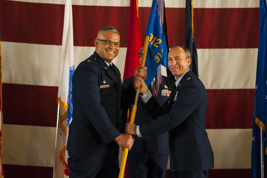 U.S. Air Force Lt. Col. Scott D. Cline, 312th Training Squadron Commander, receives the unit guideon from Col. Alejandro Ganster, 17th Training Group Commander, during the 312th TRS change of command at the Louis F. Garland Department of Defense Fire Academy High Bay Fire Academy high bay on Goodfellow Air Force Base, Texas, July 10, 2017. The change of command ceremony is a time honored military tradition that signifies the orderly transfer of authority. (U.S. Air Force photo by Senior Airman Scott Jackson/Released)