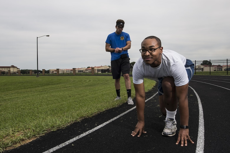 Josh Hale, 42nd Force Support Squadron personal trainer, starts his stop watch as Senior Airman Christopher Snowden, 42nd Command Post command and control operations specialist, trains for his physical training test, June 27, 2017, Maxwell Air Force Base, Ala. After failing an Air Force Physical Training test, Snowden sought out the help of Hale, who helped him improve his run time by one minute and 15 seconds in only three weeks. (U.S. Air Force photo/ Senior Airman Alexa Culbert)