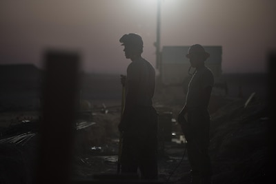 Airmen assigned to the 557th Expeditionary RED HORSE, wait for further instructions while working on a construction site June 27, 2017, in Southwest Asia. The squadron is tasked with constructing a new 332nd Air Expeditionary Wing mission support industrial complex and life support area, to include facilities, utilities and roads, providing the wing with increased capabilities. (U.S. Air Force photo/Senior Airman Damon Kasberg)