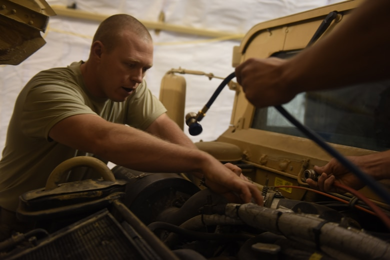 U.S. Air Force Staff Sgts. Shawn Benton, an aerospace ground equipment craftsman, and. Adam Martin, a fire truck maintenance specialist, both deployed in support of Combined Joint Task Force – Operation Inherent Resolve and assigned to the 370th Air Expeditionary Advisory Group, Detachment 1, work together to charge the air conditioning system of a Humvee at Qayyarah West Airfield, Iraq, July 2, 2017. Benton often works outside of his scope to assist with vehicle maintenance and facility sustainment at the Air Force compound at Qayyarah West CJTF-OIR is the global Coalition to defeat ISIS in Iraq and Syria. (U.S. Air Force photo by Tech. Sgt. Jonathan Hehnly)