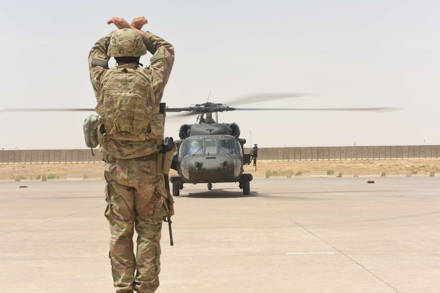 U.S. Air Force Tech. Sgt. Joseph Tenebruso, the expeditionary maintenance flight chief deployed in support of Combined Joint Task Force – Operation Inherent Resolve and assigned to the 370th Air Expeditionary Advisory Group, Detachment 1, marshals in an UH-60 Black Hawk helicopter at Qayyarah West Airfield, Iraq, July 2, 2017. The expeditionary maintenance liaisons marshal incoming aircraft at Qayyarah West to maintain an efficient parking plan at the logistical hub for the Mosul offensive. CJTF-OIR is the global Coalition to defeat ISIS in Iraq and Syria. (U.S. Air Force photo by Tech. Sgt. Jonathan Hehnly)