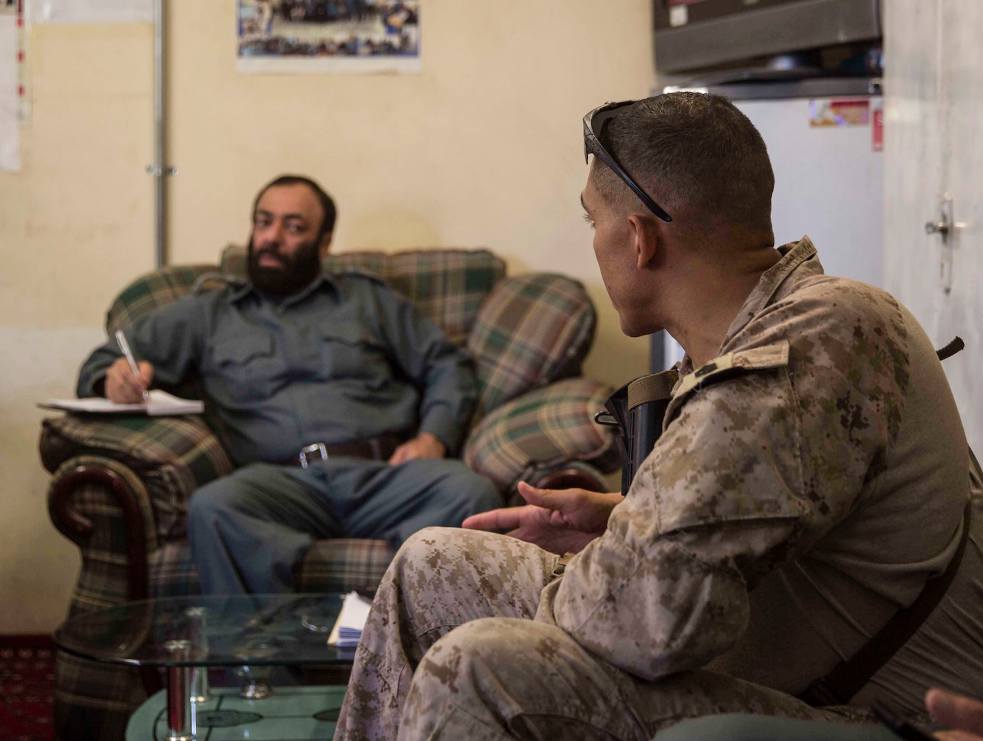 A U.S. Marine advisor with Task Force Southwest speaks with his counterpart during a train, advise and assist mission at the Helmand Provincial Police Headquarters in Lashkar Gah, Afghanistan, July 9, 2017. This mission provided an opportunity for advisors to meet with their counterparts, review the security posture at the PHQ and ensure that Afghan National Defense and Security Forces have an effective defense of Lashkar Gah. (U.S. Marine Corps photo by Sgt. Justin T. Updegraff)