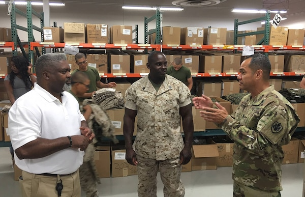 DLA Senior Enlisted Leader Command Sgt. Maj. Charles Tobin, right, discusses the logistics of uniform issue with Rick Green, DLA Troop Support, and Staff Sgt. Brown, Marine Corps Recruiting Station San Diego.