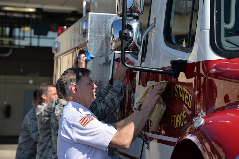 Firefighters and guests in attendance dry the new brush truck during the fire department's truck christening ceremony July 6, 2017, at Malmstrom Air Force Base, Mont. The truck can carry 500 gallons of water, 20 gallons of Class A foam and is capable of pumping and rolling to allow it to extinguish grass and wildfires. (U.S. Air Force photo/Airman 1st Class Daniel Brosam)