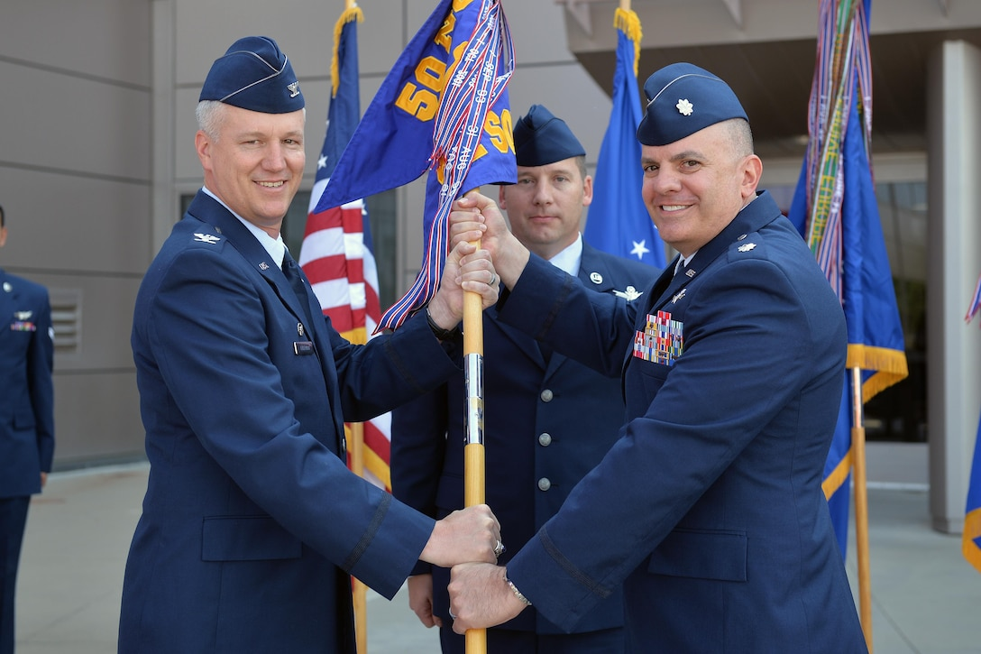 Col. William Angerman, 50th Network Operations Group commander, hands the 22nd Space Operations Squadron's guidon to the squadron's new commander, Lt. Col. Lewis Sorvillo, during the unit's change of command ceremony at Schriever Air Force Base, Colorado, Thursday, July 6, 2017. Sorvillo was preceded by Lt. Col. Terrill McCall. (U.S. Air Force Photo/Dennis Rogers)