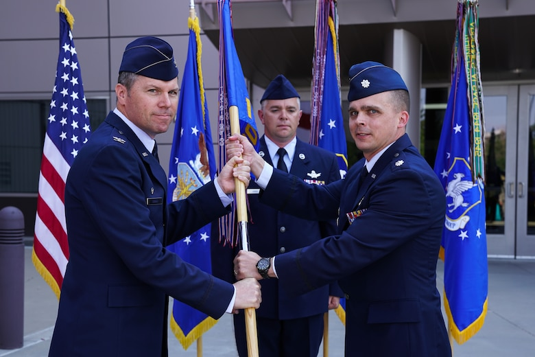 Col. Toby Doran, 50th Operations Group commander, hands the 1st Space Operations Squadron's guidon to the squadron's new commander, Lt. Col. Mark Bigley, during the unit's change of command ceremony at Schriever Air Force Base, Colorado, Friday, July 7, 2017. Bigley was preceded by Lt. Col. Casey Beard. (U.S. Air Force Photo/Christopher DeWitt)
