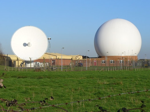 A satellite dish and dome jut out along the fence line of Royal Air Force Station Oakhanger, February 2007. A small detachment of the 23rd Space Operations Squadron is located at the station which has three antennas that allow AFSCN users to command, control and track space vehicles. (Copyright/Colin Smith)
