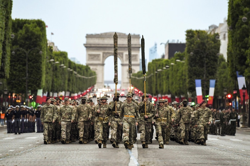 Almost 200 U.S. soldiers, sailors, Marines and airmen march from the Arc de Triomphe in Paris.