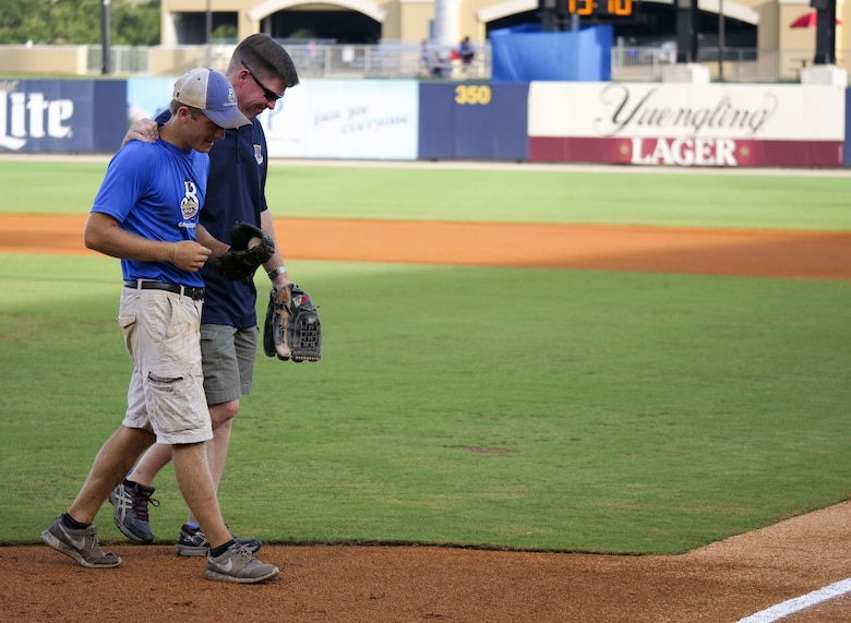 Col. C. Mike Smith, 81st Training Wing vice commander, walks off the field with his son, Mac, after throwing the first pitch during the Biloxi Shuckers Minor League Baseball team's military appreciation night July 8, 2017, in Biloxi, Miss. The Shuckers recognized and honored service members and their families for the dedication, commitment and sacrifices they make for the nation. 