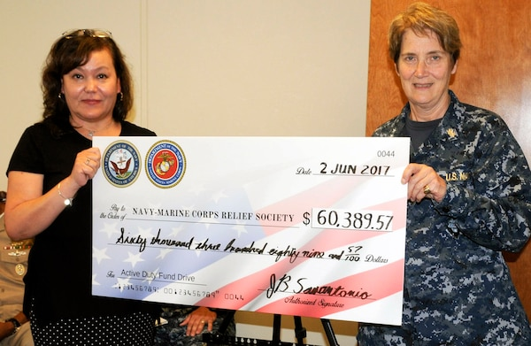 Rear Adm. Rebecca McCormick-Boyle (right), commander, Navy Medicine Education, Training and Logistics Command presents Angelica Botkin, Navy Marine Corps Relief Society director of the San Antonio office, with a check representing the money collected by Navy and Marine Corps commands in the San Antonio area during an annual fund drive. NMETLC was one of several commands to contribute and McCormick-Boyle presented the check as the senior Navy officer in the San Antonio area.