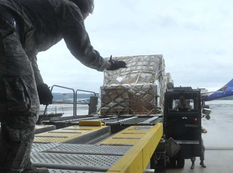 Staff Sgt. Darla Tokarski of the Wisconsin Air National Guard's 128th Logistics Readiness Squadron guides into position the 60K cargo handler driven by Staff Sgt. Tyler Cross, Air Transportation Specialist with the 81st Aerial Port Squadron out of Joint Base Charleston, S.C., at Ramstein AB, Germany, July 12, 2017.  Citizen Airmen of the 128th LRS and 81st APS performed two weeks of annual training at Ramstein in order to maintain readiness and familiarization with high-volume aerial port operations.  (U.S. Air Force photo by 1st Lt. Justin Clark)