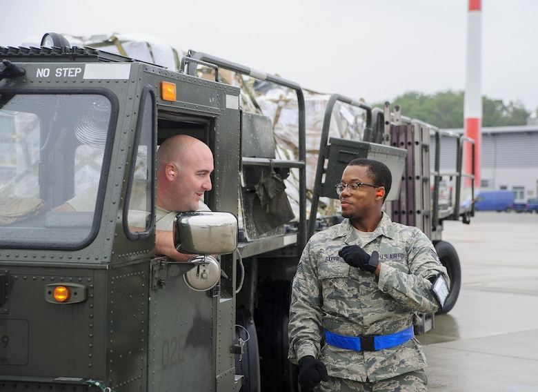 Staff Sgt. Anthony Pokorny and Senior Airman Ronnie Baker, Air Transportation Journeymen with the 81st Aerial Port Squadron out of Joint Base Charleston, S.C., prepare to offload air cargo on the ramp at Ramstein AB, Germany, July 12, 2017.  Citizen Airmen of the 81st APS performed two weeks of annual training at Ramstein in order to maintain readiness and familiarization with high-volume aerial port operations.  (U.S. Air Force photo by Senior Airman Jonathan Lane)