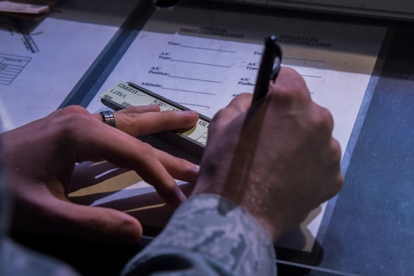 Senior Airman Anthony Carmignani, 375th Operational Support Squadron air traffic controller, writes out flight information including direction of takeoff, depart time, call signs, and type of aircraft on Aug. 9, 2016 at Scott Air Force Base, Ill. The strips help the air traffic controllers keep track of mulitple aircraft and are a reference for needed info during communications. (U.S. Air Force Photo by Airman Daniel Garcia)