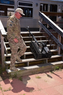 Chief Master Sgt. Ed Smith, explosive ordnance disposal program manager with the Air National Guard's 115th Fighter Wing in Madison, Wis. monitors the progress of EOD specialists using a TALON tracked military robot to remotely inspect a simulated improvised explosive device during the Audacious Warrior exercise at Fort McCoy, Wis., July 27, 2017. The 12 day long exercise utilized the extensive training facilities of Volk Field Combat Readiness Training Center and Fort McCoy Total Force Training Center to provide EOD teams from eight different states comprehensive classroom and scenario based training in EOD tactics and procedures difficult to obtain at their respective home stations. (U.S. Air National Guard Photo by Master Sgt. Paul Gorman)